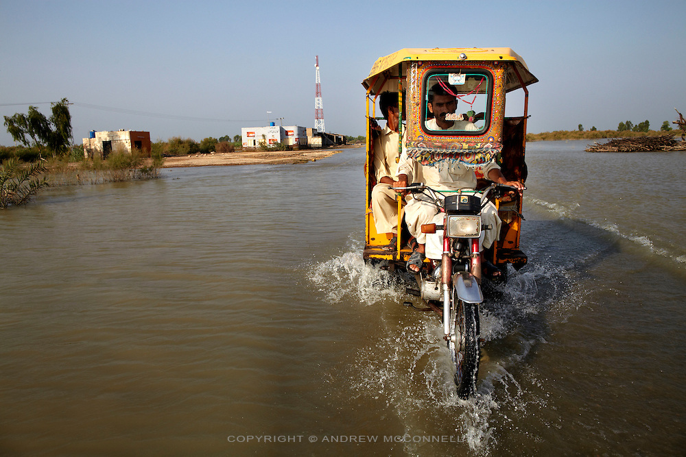 A rickshaw travels along a flooded road near Sukker, in Sindh province, Pakistan.