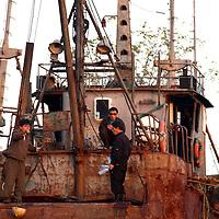 SHINIUJU, OCTOBER-26: North Korean workers sit on a boat in the port of Shiniuju ,North Korea ,October 26,2006.