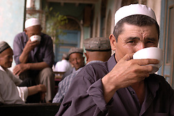 Muslim Uyghur men drinking tea in traditional teahouse in Kashgar Xinjiang Province, China
