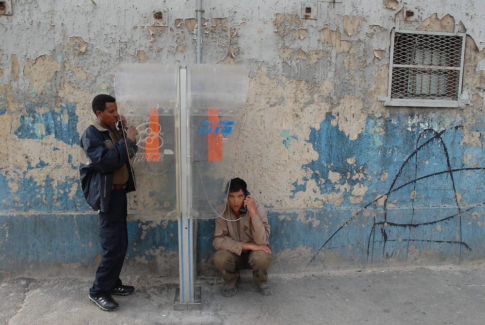 Foreign workers are talking on street phones in Neve Shaanan, Tel-Aviv. Neve Sha'anan is one of Tel Aviv's oldest neighborhoods. It is also a major transportation hub, containing both the new and old Tel Aviv Central Bus Stations. Neve Sha'anan is also Tel Aviv's red-light district, with numerous brothels. As such, many foreign workers live or look for work in Neve Sha'anan. Feb 29, 2008. Photo by Gili Yaari  *** Local Caption *** ðååä ùàðï, úçðä îøëæéú äéùðä, àåèåáåñ, òåáãéí æøéí, ñéðéí, àåôðééí,..îäâøéí, òåðé