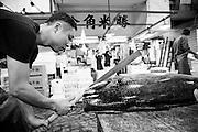 Hideto Takeda is cutting tuna at the wholesaler Maguro Naito at the Tsukiji Market, Tokyo, Japan.