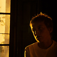 A teenage boy sitting quietly in a room with summer sunlight shining through a window