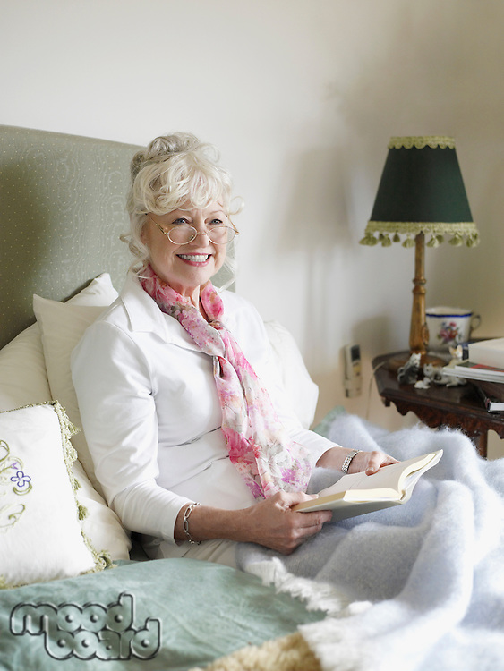 Senior woman sitting on bed reading book