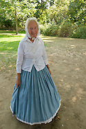 Old Bethpage, New York, U.S. 31st August 2013.  JULIETTE FOX, of Hicksville, is wearing a white hand embroidered blouse and a blue hoop skirt that are in the style of Civil War clothing, during the Olde Time Music Weekend at Old Bethpage Village Restoration, where popular music of the American Civil War period is performed, and visitors learn traditional 1800's contradances.