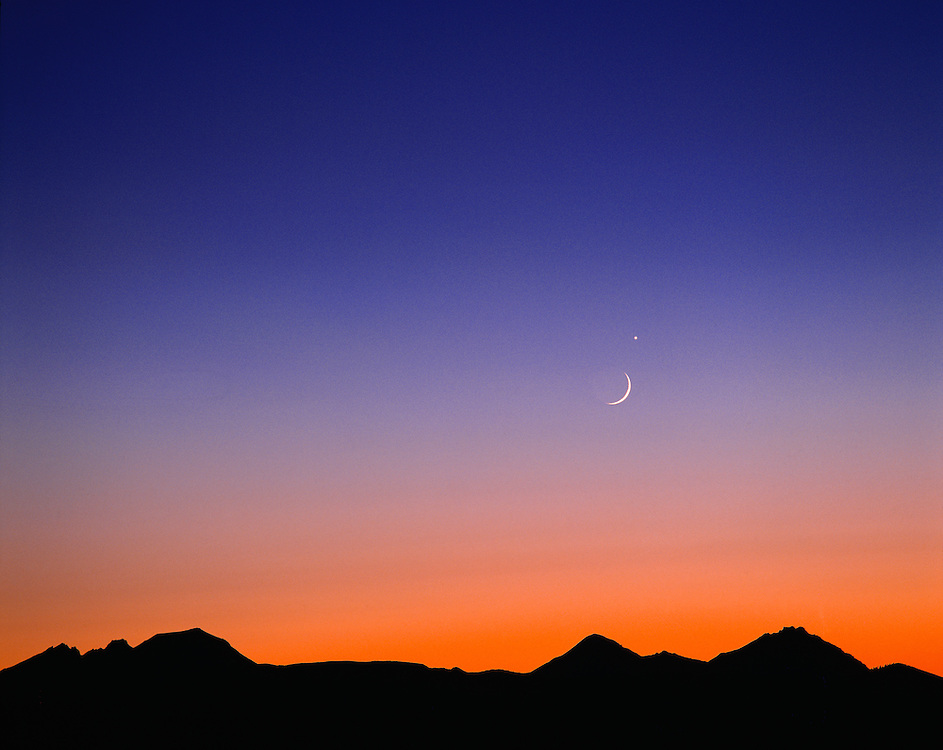 A crescent moon hangs above the silhoutted Cascade range with Venus as its beauty mark, Oregon. ©Ric Ergenbright