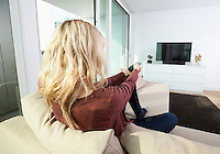 Rear view of young woman watching television on sofa at home
