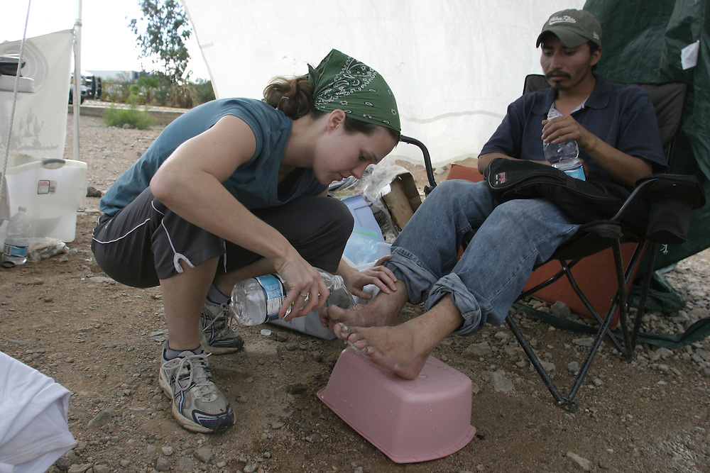 Sara, 24, a volunteer with the No More Deaths humanitarian organization, gives medical aid to an undocumented immigrant caught by the border patrol in Arizona and sent back to the Mexican side of the border town of Nogales on 14 July 2006... ..