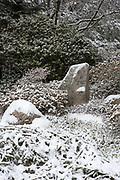 Snow falling on stones set in the Japanese style, Asticou Azalea Garden, Northeast Harbor, Maine.