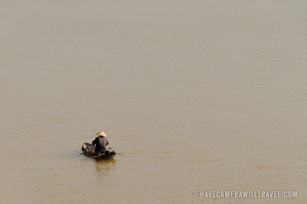 A fisherman in his small wooden fishing boat on the Perfume River in Hue, Vietnam.