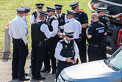 London, UK. 19th April, 2019. A group of senior police officers meets alongside the main motorway approach to Heathrow airport following a small protest earlier by Extinction Rebellion Youth. A large policing operation was put in place in and around the airport in preparation for expected protests by climate change activists from Extinction Rebellion. Only a very small symbolic protest by teenage activists from Extinction Rebellion Youth took place, dispersed by police officers under threat of arrest.