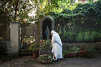 ROME, ITALY - 27 AUGUST 2016: A sister of the Missionaries of Charity, the religious congregation founded by Mother Teresa in 1950, throws flowers at a statue of the Holy Mary, by the accommodation center ran by the Missionaries of Charity at San Gregorio al Celio in Rome, Italy, on August 27th 2016.<br /> <br /> Mother Teresa, also known as Blessed Teresa of Calcutta, was an Albanian Roman Catholic nun and missionary. She founded the Missionaries of Charity, a Roman Catholic religious congregation, whose members must adhere to the vows of chastity, poverty, and obedience, as well as the vow to give wholehearted free service to the poorest of the poor. Shortly after she died in 1997, Pope John Paul II waived the usual five-year waiting period and allowed the opening of the process to declare her sainthood. She was beatified in 2003. A second miracle was credited to her intercession by Pope Francis, in December 2015, paving the way for her to be recognised as a saint by the Roman Catholic Church. Her canonisation is scheduled for September 4th 2016, a day before the 19th anniversary of her death.