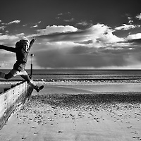 Woman jumps on beach with hands in the air, looking to camera