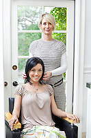 Portrait of a beautiful mid adult customer with hairstylist in beauty salon
