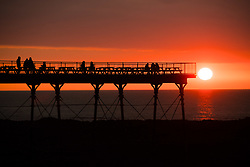 © Licensed to London News Pictures.<br /> Aberystwyth UK, 26/03/2019.<br /> A beautiful sunset , at the end of another day of warm spring sunshine, silhouettes people on the pier in Aberystwyth, on the Cardigan Bay coast of west Wales. High pressure continues to dominate the weather for much of the UK, with settled conditions and clear blue skies<br /> photo Keith Morris/LNP