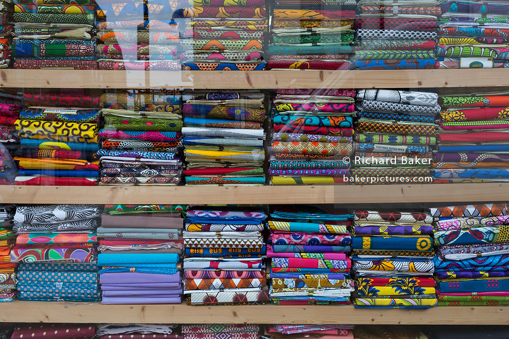 Sagging shelves, heavy with the weight of imported colourful fabrics in an East End street, on 14th February 2018, in London, England.