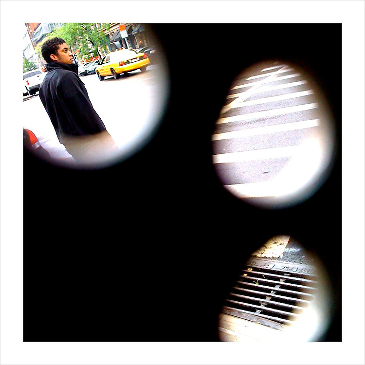 A view from the inside of a NYC telephone booth, looking out through the little holes. (iPhone image)