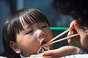 Yeouido Island. Feeding kid with chopsticks during sunday family excursion.