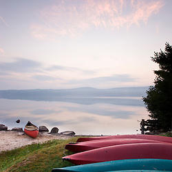 Canoes and kayaks on the shoreline of Lake Sunapee at sunrise at Mount Sunapee State Park in Newbury, New Hampshire.