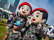 "13 JANUARY 2018 - BANGKOK, THAILAND:      Thai army mascots pose with a child during Children's Day activities at the Royal Thai Army's King's Guard 2nd Cavalry Camp in central Bangkok. Children's Day is called ""Wan Dek"" in Thai. Many government offices and military bases hold special activities for children as do shopping malls.  PHOTO BY JACK KURTZ"