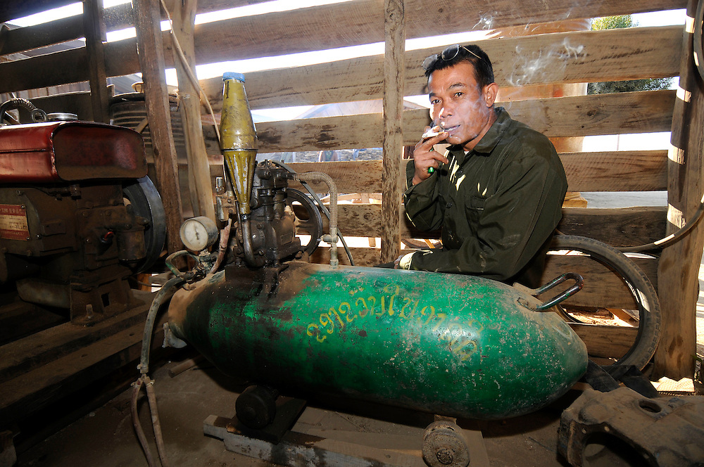 Mr. Boonmi with his bomb compressor made from a US 750 lb framentation bomb left over from the US and Vietnamese secret war in Phou Vieng, Laos.  He dismantled the live bomb which uses a Russian rocket propelled grenade for a carburetor.  The invading North Vietnamese Army destroyed the historic town in nearby Muang Sui.