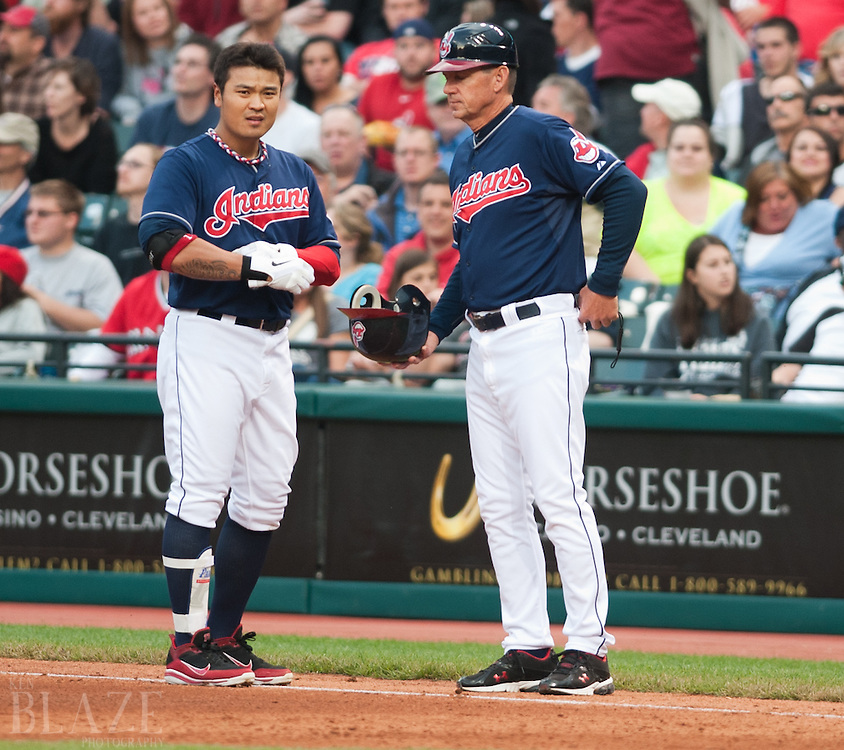CLEVELAND, OH USA - MAY 8:  Cleveland Indians right fielder Shin-Soo Choo (17) hands his helmet to Cleveland Indians first base coach Tom Wiedenbauer (20) after grounding out  during the fourth inning at Progressive Field in Cleveland, OH, USA on Tuesday, May 8, 2012.