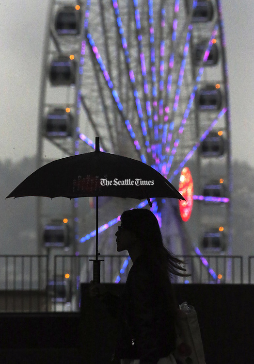 A pedestrian along First Avenue in downtown Seattle passes the Seattle Great Wheel, which offers a little color on a rainy day, <br />