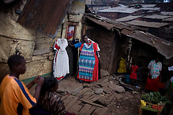 A man shows of dresses he is trying to sell in the trash filled streets in Mathare, one of the poorest slums in Nairobi.  Running water and electricity are scarce and trash and human waste fills the streets.  Many people have no jobs and those who do work can earn less than one dollar a day.