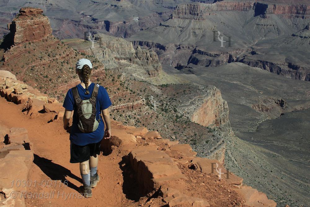 Girl hikes down South Kaibab Trail above O'Neill Butte and Tonto Platform; Grand Canyon National Park, Arizona.