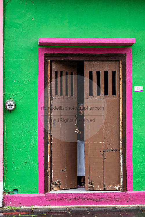 A woman peeks out from a doorway of a colorful colonnade style building in Tlacotalpan, Veracruz, Mexico. The tiny town is painted a riot of colors and features well preserved colonial Caribbean architectural style dating from the mid-16th-century.