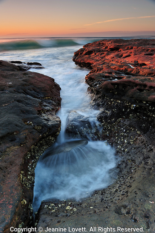 Australian Red rocks, with wave running over a rock.