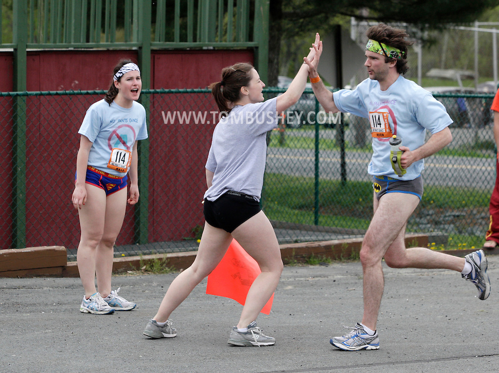 John Dwyer of Philadelphia, right, gets a high five from No Pants Dancde teammate Annie Welsh, also of Philadelphia, as Dwyer approached the end of his first leg in the Ragnar Relay in Wurtsboro on Friday, May 13, 2011.