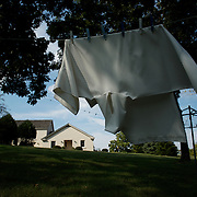 A vestment garment, worn by a priest, flaps in the breeze at Our Lady of the Mississippi Abbey, a monastery of Trappist nuns.  The nuns at the abbey launder and dry the robe for Father Xavier Dieter, who comes to the convent to preside over daily prayer services.   The community of 22 Roman Catholic women follow Jesus Christ through a life of prayer, silence, simplicity and ordinary work.  Their home is a beautiful monastery which sits high on a bluff, overlooking the Mississippi River.