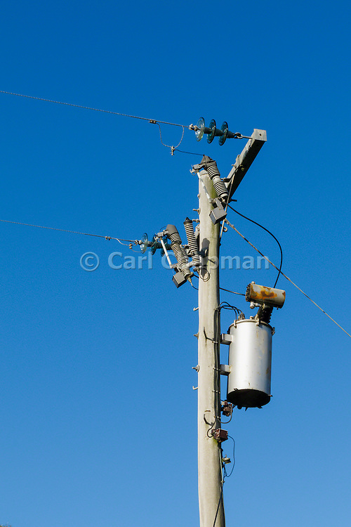 Electricity transformer, power lines and insulators on a wooden power pole.