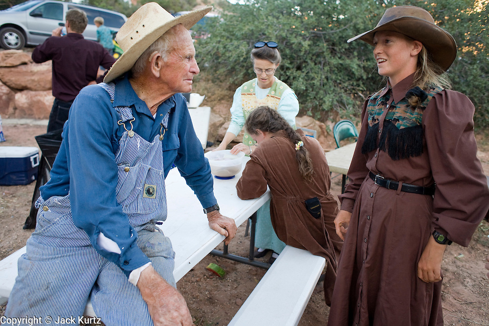 """Aug 9, 2008 -- COLORADO CITY, AZ: JOSEPH JESSOP, 86, patriarch of the Jessop family, polygamists and members of FLDS in Colorado City, AZ, talks to one of his children at their home in Colorado City.Colorado City and neighboring town of Hildale, UT, are home to the Fundamentalist Church of Jesus Christ of Latter Day Saints (FLDS) which split from the mainstream Church of Jesus Christ of Latter Day Saints (Mormons) after the Mormons banned plural marriage (polygamy) in 1890 so that Utah could gain statehood into the United States. The FLDS Prophet (leader), Warren Jeffs, has been convicted in Utah of """"rape as an accomplice"""" for arranging the marriage of teenage girl to her cousin and is currently on trial for similar, those less serious, charges in Arizona. After Texas child protection authorities raided the Yearning for Zion Ranch, (the FLDS compound in Eldorado, TX) many members of the FLDS community in Colorado City/Hildale fear either Arizona or Utah authorities could raid their homes in the same way. Older members of the community still remember the Short Creek Raid of 1953 when Arizona authorities using National Guard troops, raided the community, arresting the men and placing women and children in """"protective"""" custody. After two years in foster care, the women and children returned to their homes. After the raid, the FLDS Church eliminated any connection to the """"Short Creek raid"""" by renaming their town Colorado City in Arizona and Hildale in Utah. A member of the Jessop family weeds the community corn plot in Colorado City, AZ. The Jessops are a polygamous family and members of the FLDS. Photo by Jack Kurtz / ZUMA Press"""