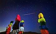 A meteor streaks across the sky with  Ugo Rondinone's Seven Magic Mountains art installation in the foreground during a Perseid<br />