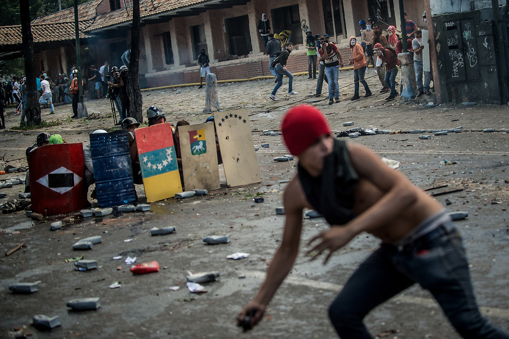 CARACAS, VENEZUELA - JULY 26, 2017: Members of La Resistencia throw molotov cocktails and rocks at soldiers, who responded with tear gas, rubber bullets and buckshot, during an anti-government protest to demand that the National Constituent Assembly election scheduled for Sunday, July 30th be cancelled. The political opposition called for a 48 hour national strike on July 26th and 27th, and for their supporters to close businesses, not go to work, and instead create barricades to block off their streets.  Opposition controlled areas of the country were completely shut down.  The strike was called as part of the opposition's civil resistance movement - that began on April 1st, to protest against the Socialist government's attempt to elect a new assembly that will have the power to re-write the constitution, and their opposition to the Socialist's continued threats to Venezuelan Democracy.  PHOTO: Meridith Kohut for The New York Times