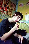 Teenage boy rolling a spliff joint in his bedroom football posters on the wall Lambeth Walk South London c.2000