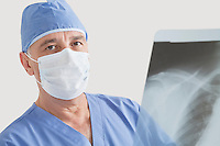 Portrait of senior male surgeon examining x-ray over gray background