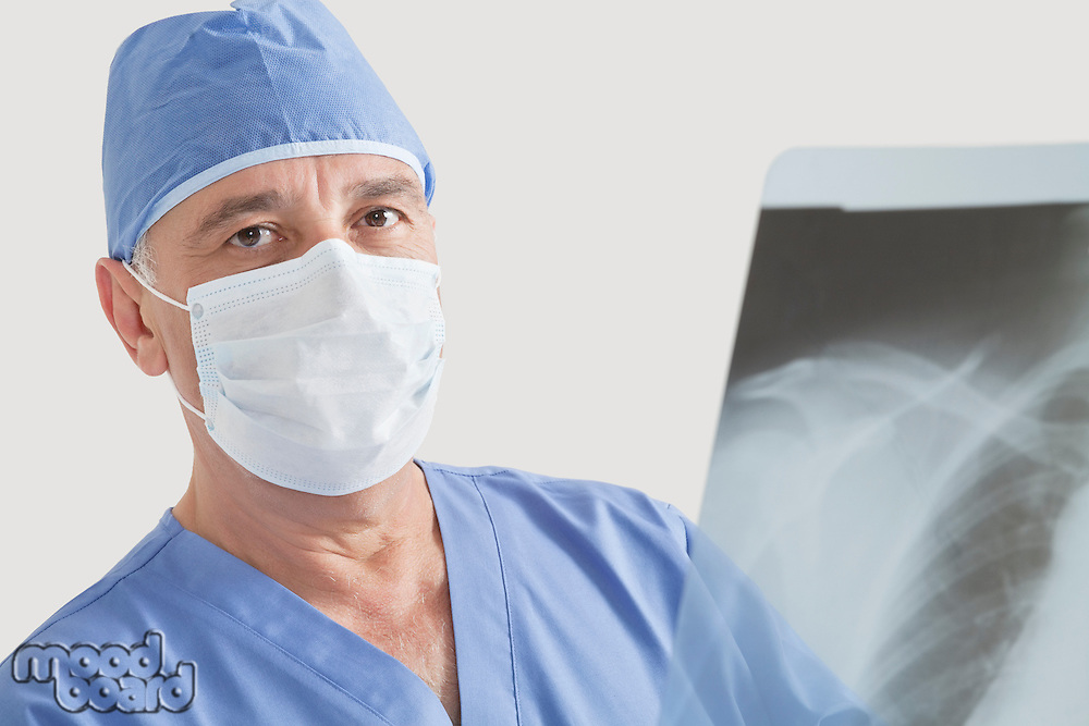 Portrait of senior male surgeon examining x-ray over gray background