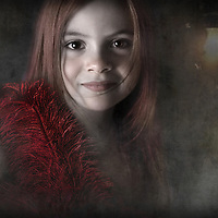young child in a room with a lightbulb wearing red feathers