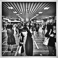 Commuters are steps away from stepping outside of Shinjuku Station but not before a security camera looks them over one more time.  Shinjuku Station, Tokyo, Japan.