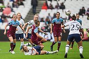 Martha Thomas (West Ham) falling onto the pitch with ball heading to Hannah Godfrey (Tottenham Hotspur) during the FA Women's Super League match between West Ham United Women and Tottenham Hotspur Women at the London Stadium, London, England on 29 September 2019.