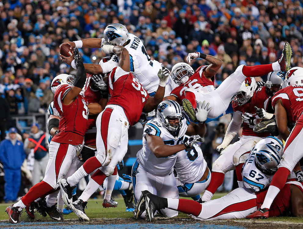 CHARLOTTE, NC - JAN 24: Quarterback Cam Newton #1 of the Carolina Panthers leaps over members of the Arizona Cardinals defense for a touchdown during the NFC Championship game at Bank of America Stadium on January 24, 2016 in Charlotte, North Carolina.