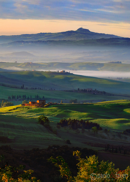 A glorious sunrise on the rolling hills of the Orcia Valley in Tuscany, Italy, with the fortress and tower of Radicofani in the background. Taken on an early morning at the end of April moments after sunruse, from the bastions of Pienza.