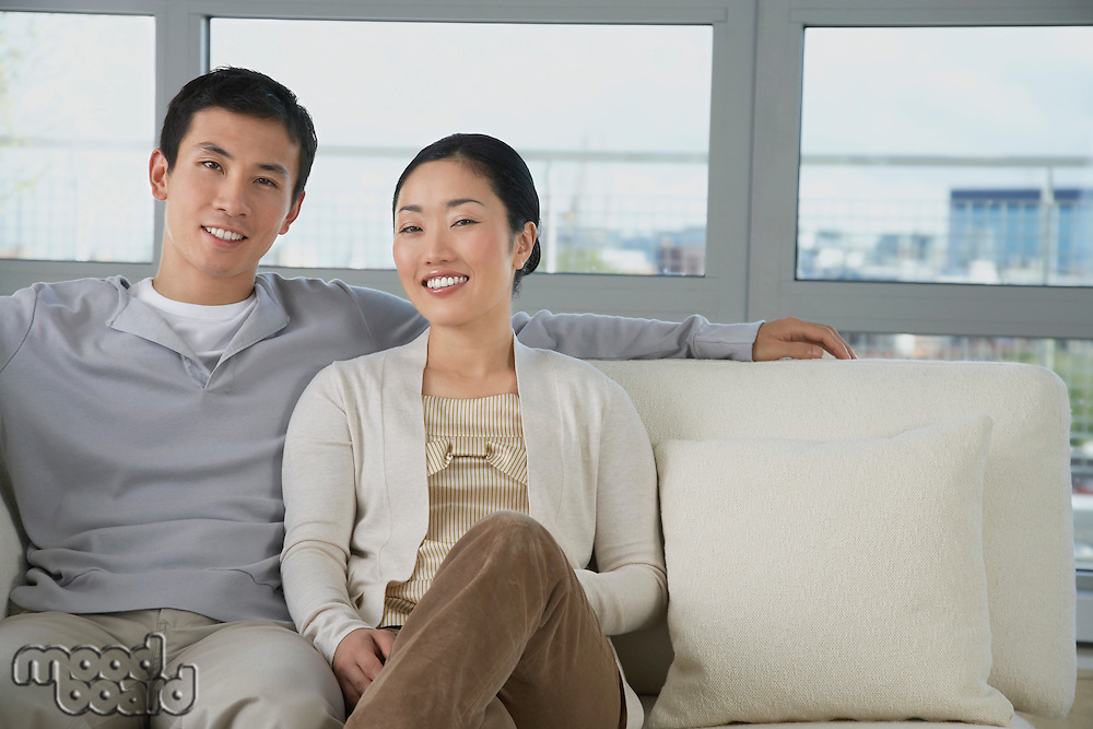 Husband Relaxing arm behind wife on Sofa