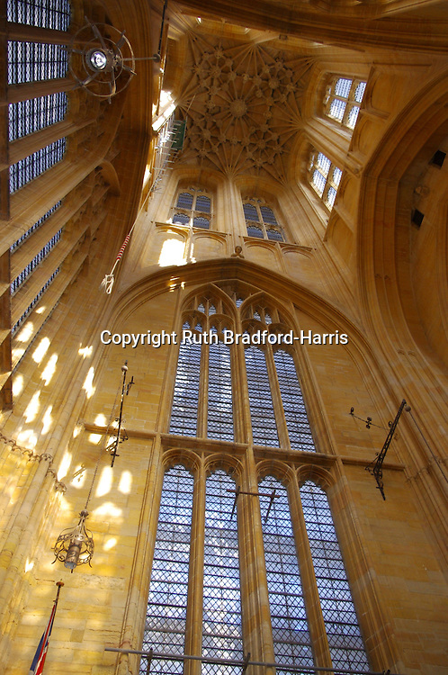 Looking up into the tower of St.Botulph's church ('Boston Stump'). Morning sunlight illuminates the golden Gothic stone tracery and carved ceiling (installed in 1851-53 to the original plan by 1851 to 1853 by George Gilbert Scott), casting reflections and shadows onto the walls. The blue sky and white clouds outside are seen through the tall windows. <br /> <br /> At 272 feet, the Medieval tower is one of tallest in England, visible for miles across the flat surrounding fenland. Only 33 feet from the River Haven, the tower has never required any addition support thanks to the remarkable skill of the original Medieval builders. Externally, the tower is capped with a decorative stone octagonal lantern fringed with pinnacles, each sporting a golden wind vane (please see my other images in this gallery). Lights were once lit in the lantern to guide ships at sea in The Wash.<br /> <br /> Date taken: 17 September 2011.