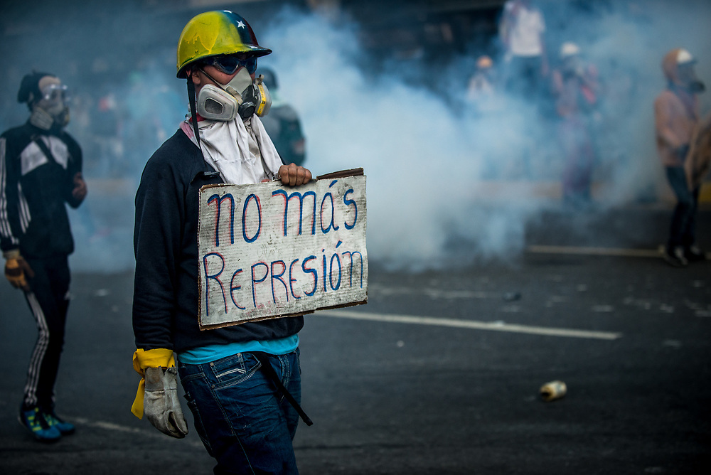 "CARACAS, VENEZUELA - MAY 20, 2017:  An anti-government protester walks with a sign that says, ""No more repression"" during clashes with security forces. The streets of Caracas and other cities across Venezuela have been filled with tens of thousands of demonstrators for nearly 100 days of massive protests, held since April 1st. Protesters are enraged at the government for becoming an increasingly repressive, authoritarian regime that has delayed elections, used armed government loyalist to threaten dissidents, called for the Constitution to be re-written to favor them, jailed and tortured protesters and members of the political opposition, and whose corruption and failed economic policy has caused the current economic crisis that has led to widespread food and medicine shortages across the country.  Independent local media report nearly 100 people have been killed during protests and protest-related riots and looting.  The government currently only officially reports 75 deaths.  Over 2,000 people have been injured, and over 3,000 protesters have been detained by authorities.  PHOTO: Meridith Kohut"