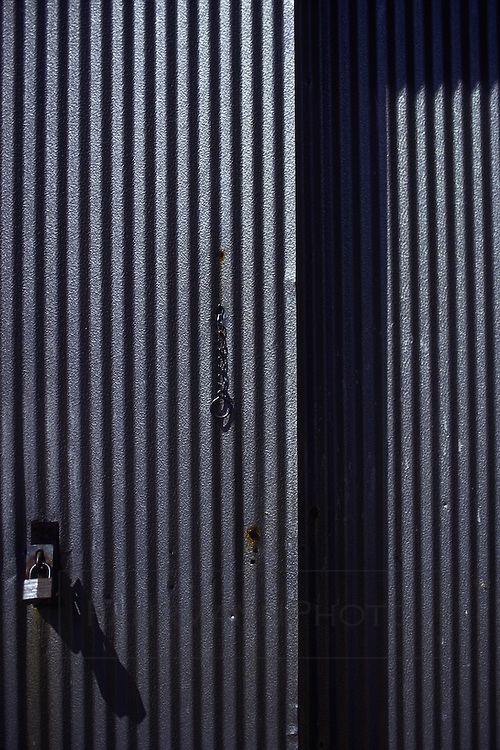 Corrugated steel door with hardware and padlock that is slightly opened