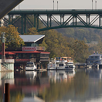 The Tennessee River flows thru Knoxville, Tn. with the Gay Street Bridge in the background. One of Knoxville's favorite restaurants -Calhoun's on the River sets on the shoreline just beyond Volunteer Landing.