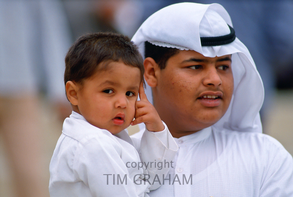 Father carrying his son, Kuwait